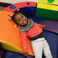 Toddler smiling in a colorful classroom.
