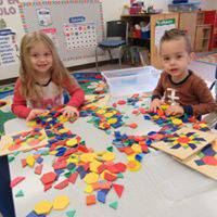 Young children playing with learning materials in a classroom.